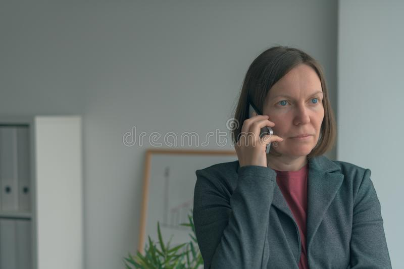 Ernstige onderneemster die op mobiele telefoon in bureau spreken royalty-vrije stock foto