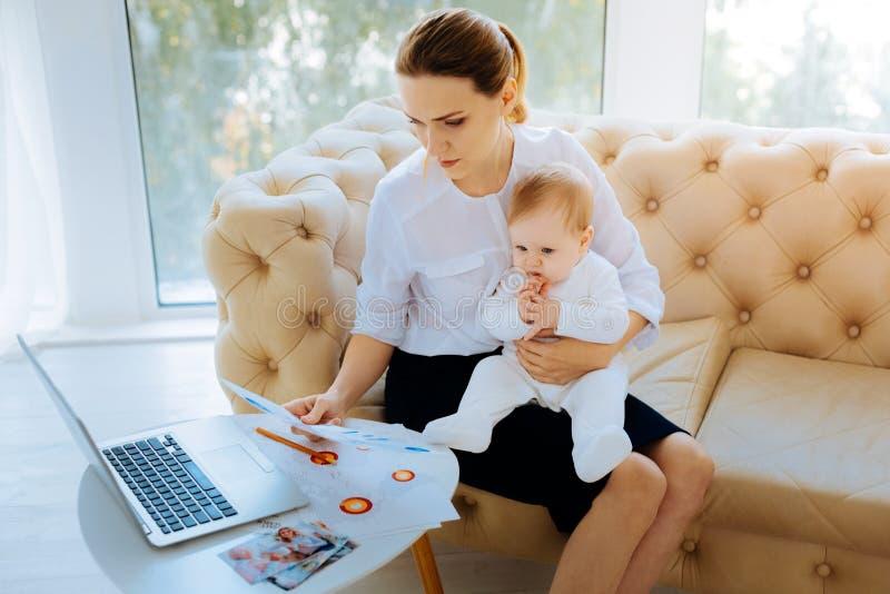 Ernstige onderneemster die thuis terwijl het zitten met een baby werken stock foto's
