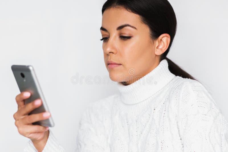 Ernstige ongelukkige jonge aantrekkelijke vrouw die smartphone over witte achtergrond met behulp van Portret van mooie vrouw die  stock foto