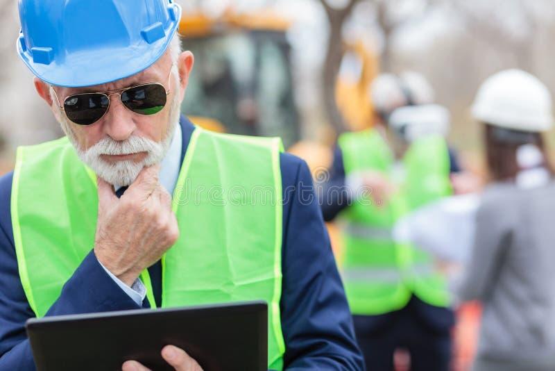 Ernstige, ongerust gemaakte, hogere grijze haired ingenieur of zakenman die aan een tablet op bouwwerf werken royalty-vrije stock foto's
