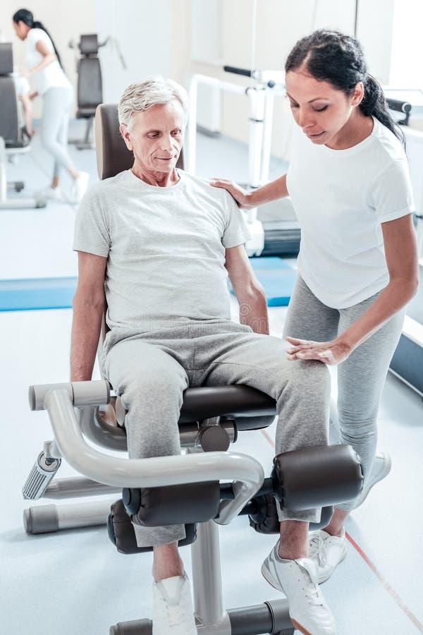 Ernstige oude mens en zijn trainer het uitoefenen stock foto