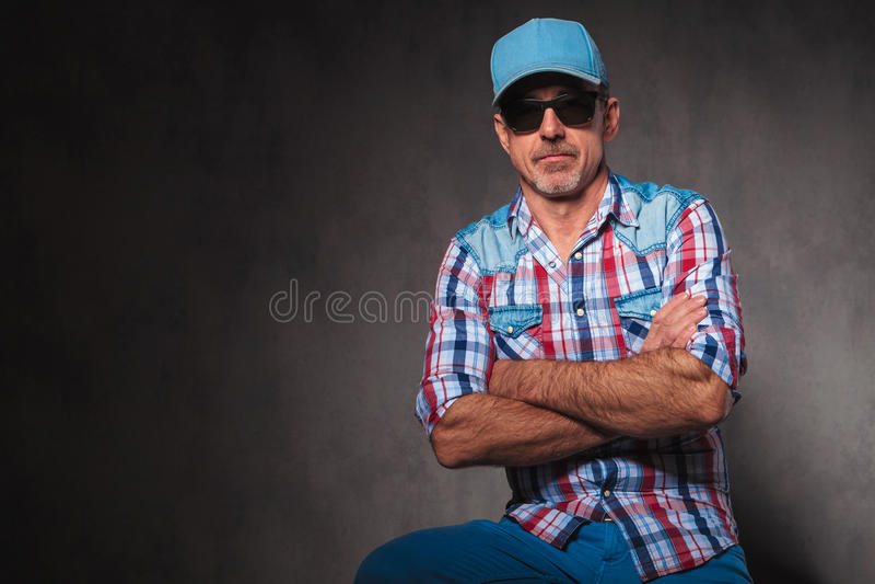 Ernstige oude toevallige mens die zonnebril en sitti van de honkbalhoed dragen royalty-vrije stock afbeelding