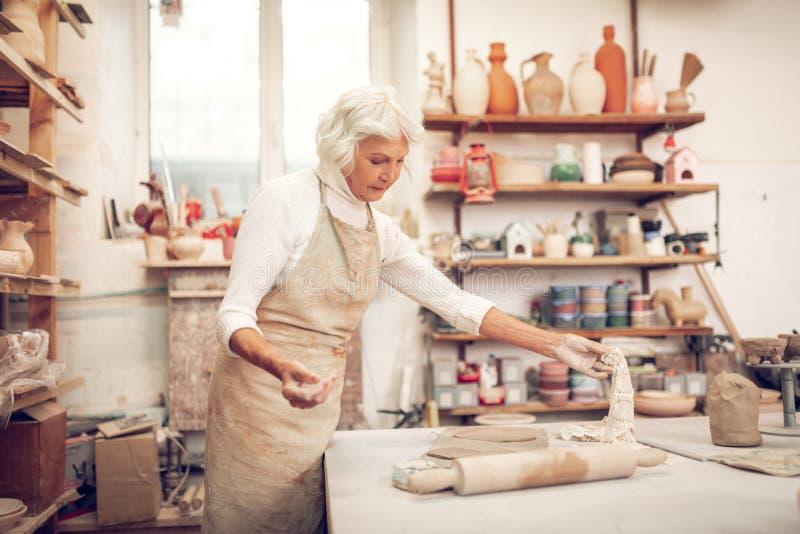 Ernstige oude vrouw die een gehaakt servet nemen royalty-vrije stock foto