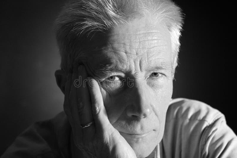 Ernstige oudere mens die camera onderzoekt royalty-vrije stock afbeeldingen