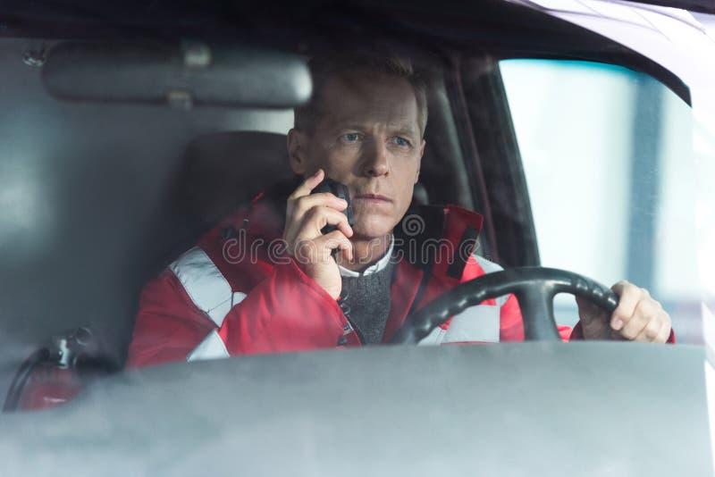 ernstige paramedicuszitting in ziekenwagen bij bestuurder zetel en het spreken stock foto