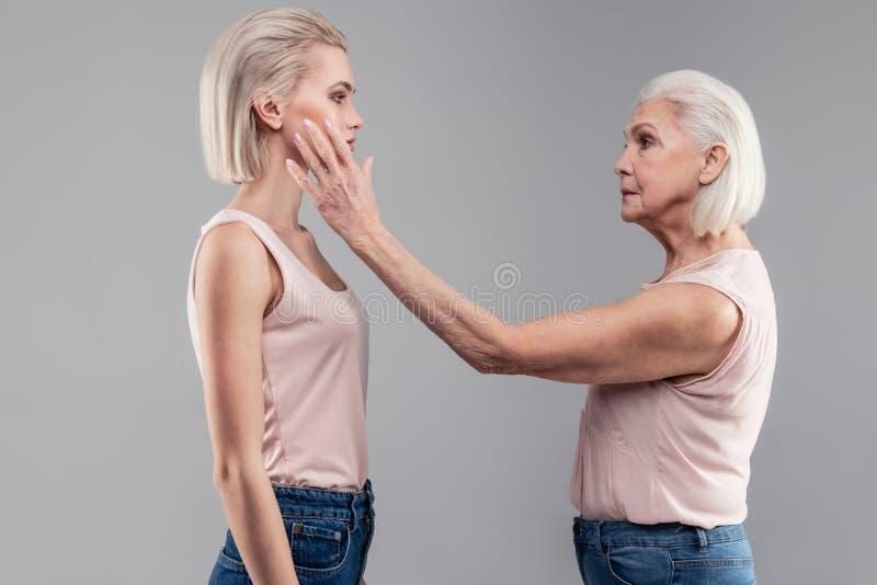 Ernstige propere hogere dame die haar kortharige jonge versie petting stock afbeeldingen