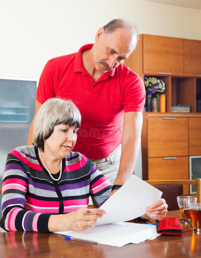Ernstige rijpe vrouw met echtgenoot die financiële documenten lezen stock foto's