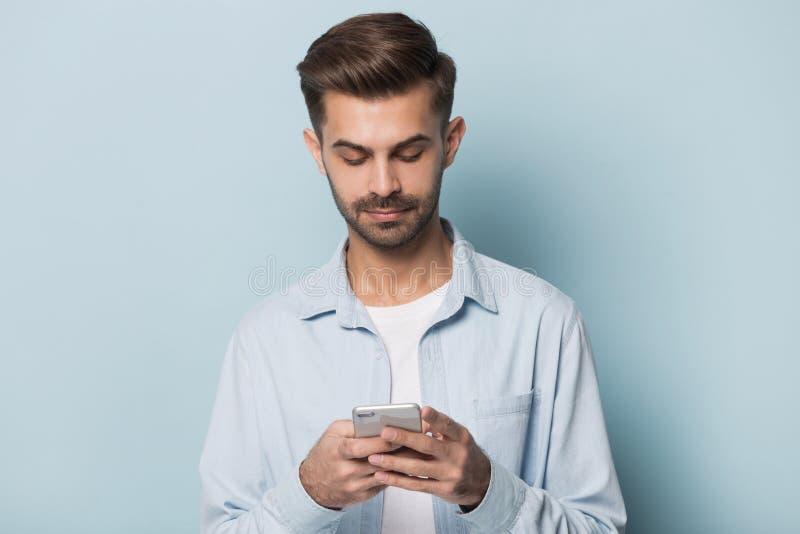 Ernstige smartphone van de kerelholding status geïsoleerd op blauwe studioachtergrond stock foto