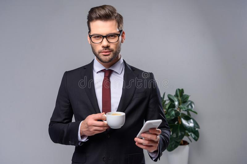 ernstige smartphone van de zakenmanholding en kop van koffie en het kijken stock foto