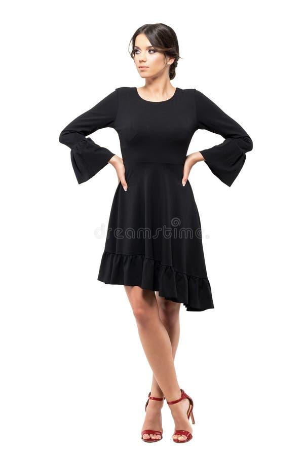 Ernstige Spaanse vrouw die in zwarte flounce kleding met handen op heupen weg kijken royalty-vrije stock afbeeldingen