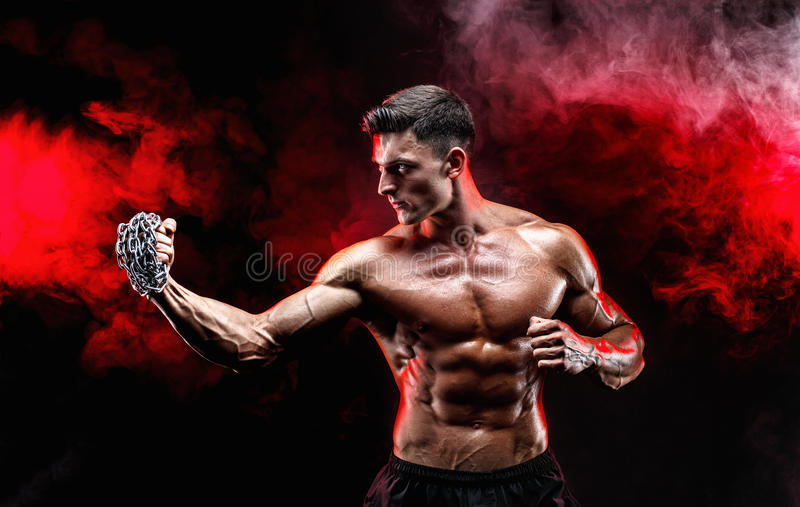 Ernstige spiervechter die die de stempel met de kettingen doen over zijn vuist worden gevlecht stock afbeelding