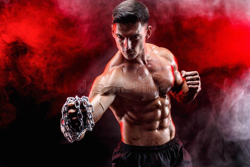 Ernstige spiervechter die die de stempel met de kettingen doen over zijn vuist worden gevlecht stock foto