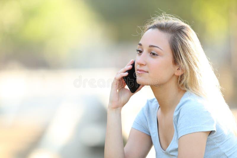 Ernstige tiener die op telefoon in een park spreken stock afbeelding