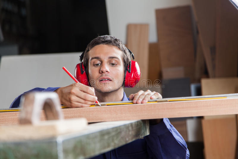 Ernstige timmerman die een stuk van hout meten stock foto