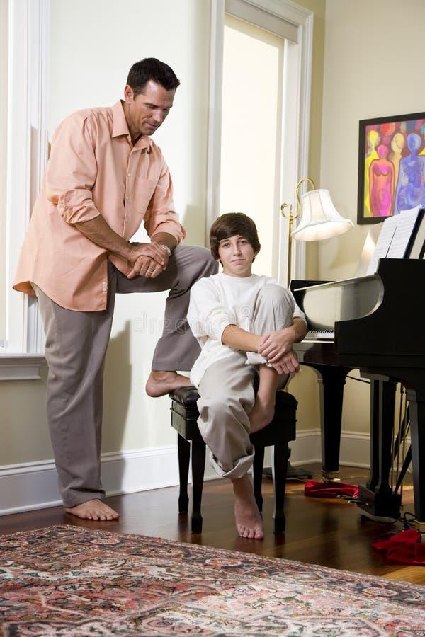 Ernstige vader die aan tienerzoon thuis spreekt royalty-vrije stock afbeeldingen