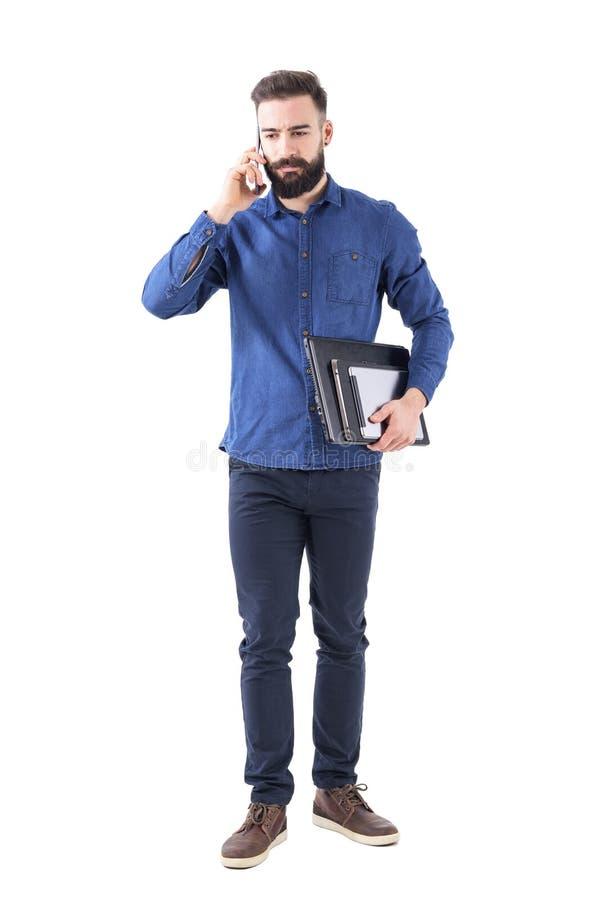 Ernstige verstoorde professionele bedrijfsmens die op telefoon dragende laptop en de tablet onder wapen spreken die neer eruit zi stock afbeeldingen