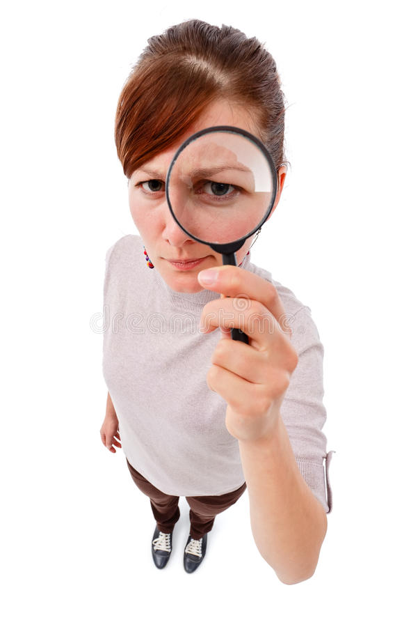Ernstige vrouw als detective met meer magnifier stock afbeelding