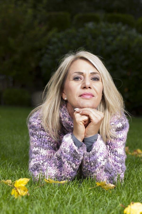 Ernstige vrouw die in gras liggen stock afbeelding