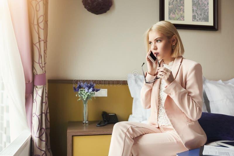 Ernstige vrouw die op telefoon in hotelruimte spreken royalty-vrije stock foto's