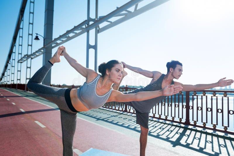 Ernstige vrouw en trainer die hun spieren stemmen royalty-vrije stock foto