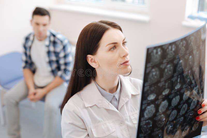 Ernstige vrouwelijke neuroloog die de Röntgenstraalfoto onderzoeken royalty-vrije stock foto's
