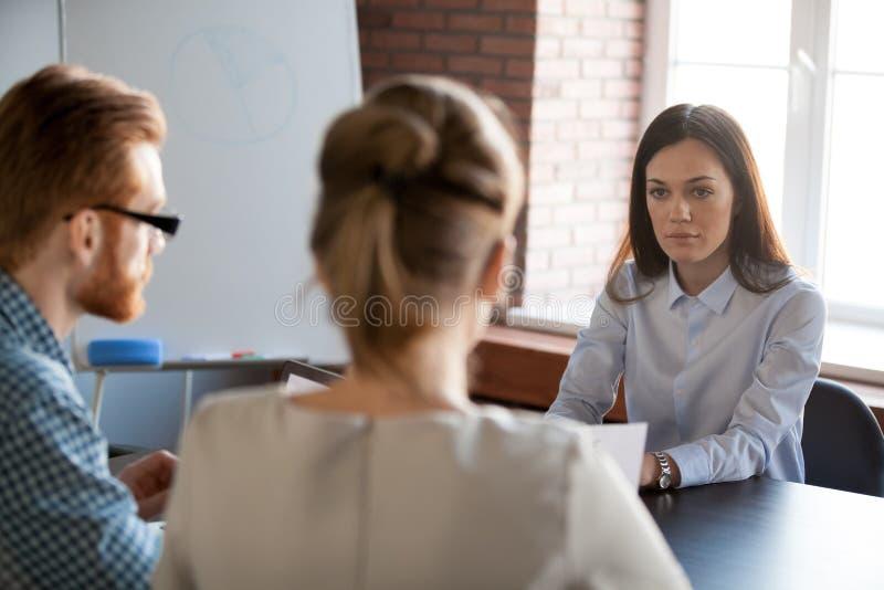 Ernstige vrouwelijke werkgever die aan werknemers luisteren die over het werk rapporteren royalty-vrije stock afbeeldingen