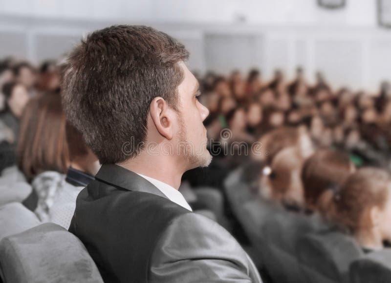 Ernstige zakenman die aan een lezing in de conferentiezaal luisteren stock afbeelding