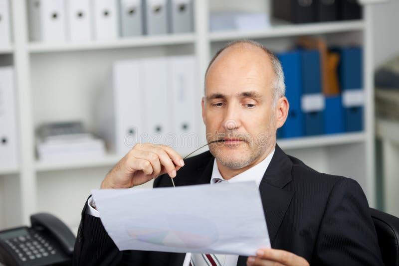 Ernstige zakenman die document bestuderen stock foto