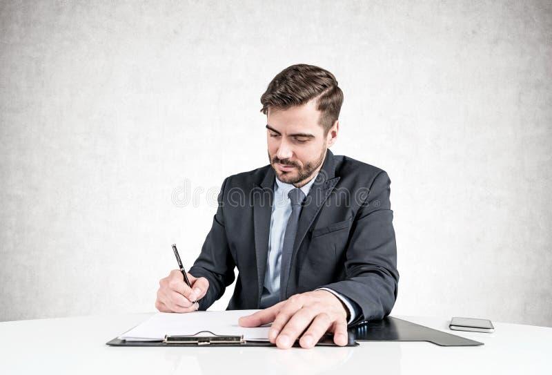 Ernstige zakenman die document ondertekenen bij lijst stock fotografie