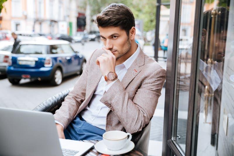 Ernstige zakenman die moderne laptop in koffiewinkel met behulp van stock foto's
