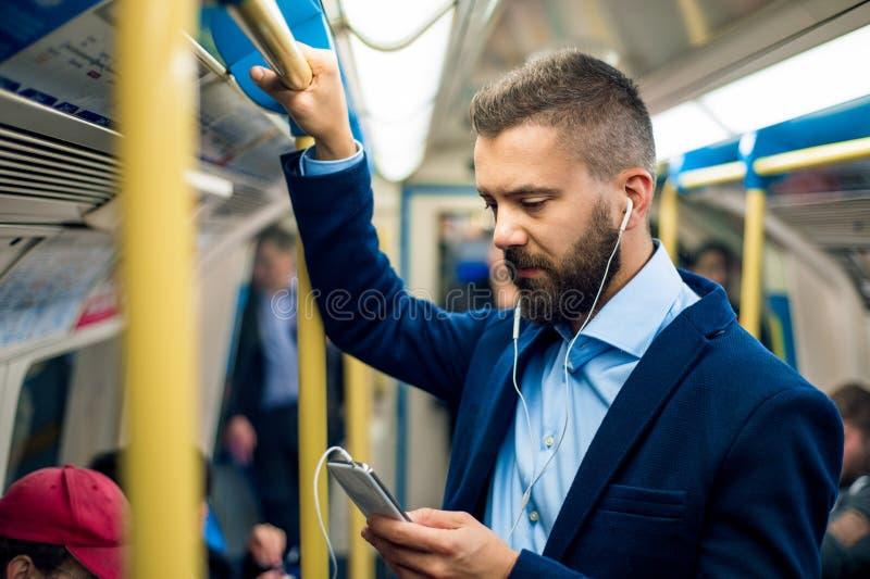 Ernstige zakenman die naar het werk reizen Status binnen undergro stock fotografie