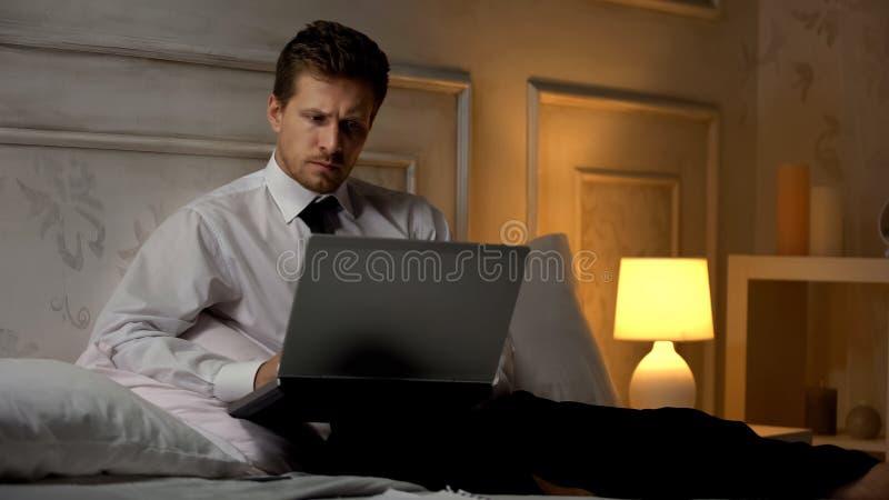 Ernstige zakenman die toespraak voor vergadering voorbereiden, die met computer bij nacht werken stock fotografie