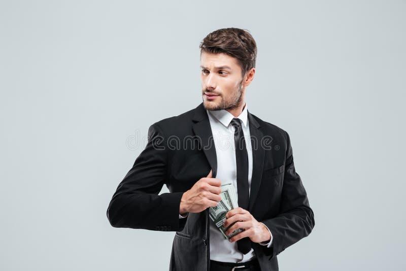 Ernstige zakenman in kostuum en band verbergend geld in zak stock afbeelding