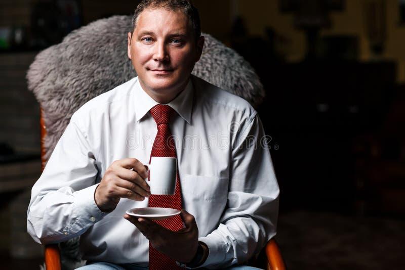 Ernstige zakenman op middelbare leeftijd met koffiekop stock foto