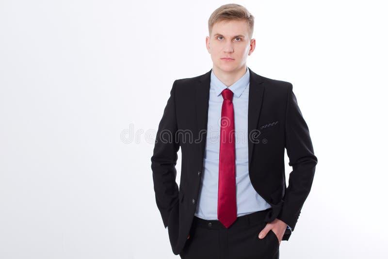 Ernstige zakenman in zwart kostuum en rode die band op witte achtergrond wordt geïsoleerd Bedrijfs concept Exemplaarruimte en spo stock afbeelding