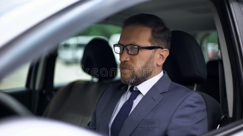 Ernstige zakenmanzitting in auto, eenzaamheid vóór het beklemtoonde werk, dag planning stock foto's