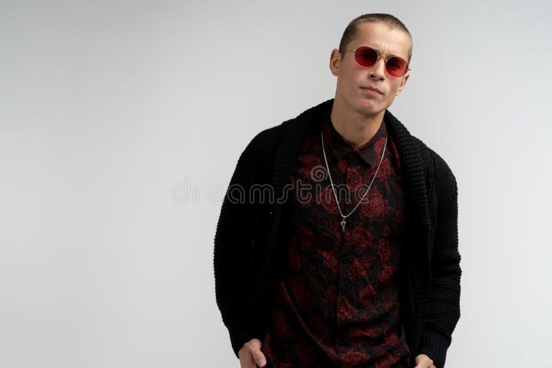 Ernstige zekere aantrekkelijke jonge mens met kort kapsel in rode zonnebril die modieuze zwarte sweater en overhemd dragen royalty-vrije stock afbeelding
