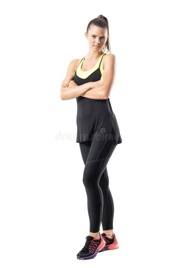 Ernstige zekere jonge actieve vrouw die in sportkleding met gekruiste wapens camera bekijken royalty-vrije stock fotografie