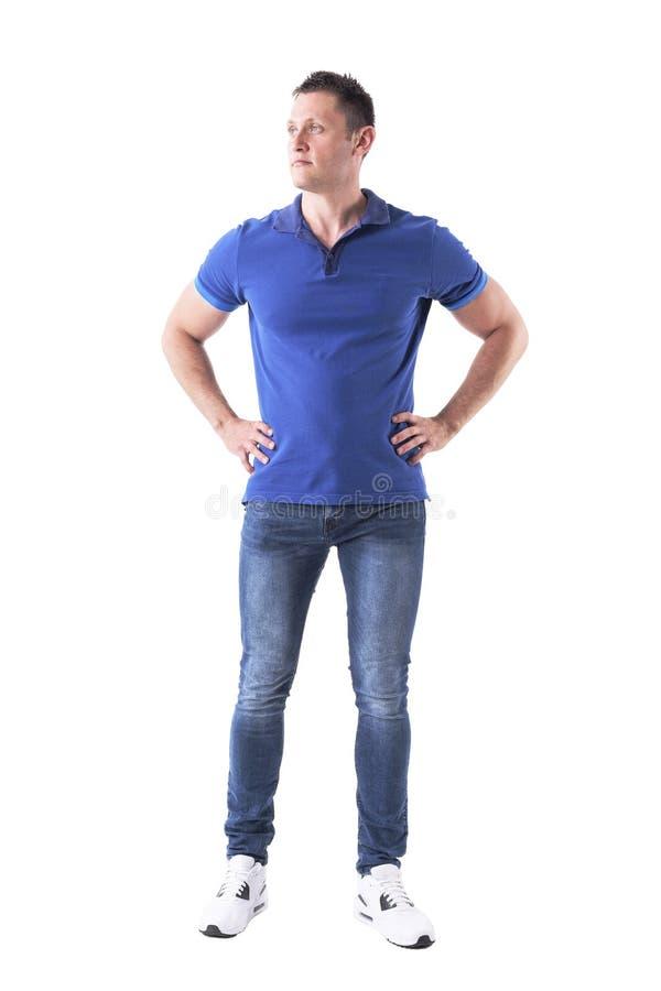 Ernstige zekere jonge volwassen toevallige mens die in blauw polooverhemd weg met wapens op heupen kijken stock foto