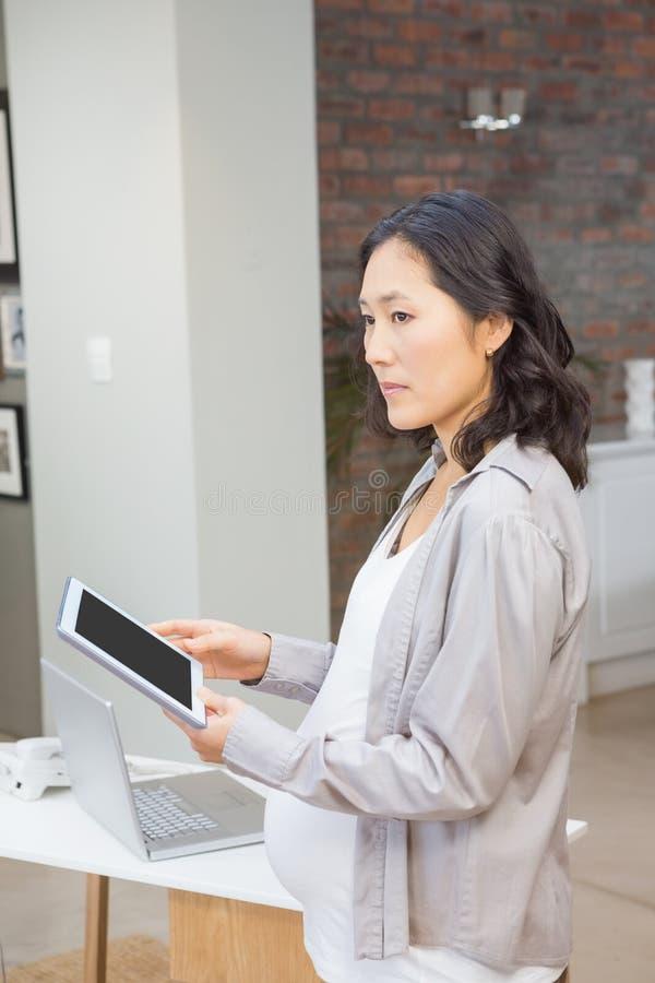 Ernstige zwangere vrouw die tablet gebruikt stock foto