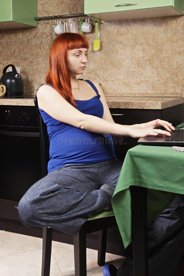 Ernstige zwangere vrouw die thuis werken stock afbeelding