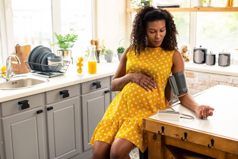 Ernstige zwangere vrouw tijdens bloeddrukmeting stock foto
