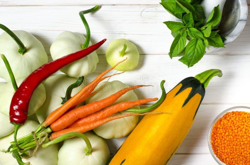 Ernte Patisons, Knoblauch, Karotten, Basilikum, Linsen und Zucchinilüge auf einem blauen Holztisch stockfotografie