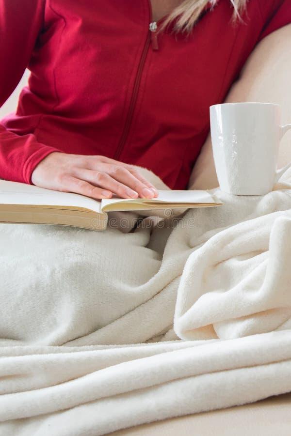 Ernteansicht der jungen erwachsenen Frau entspannt sich auf bequemem Sofa mit Buch und Heißgetränk stockfoto