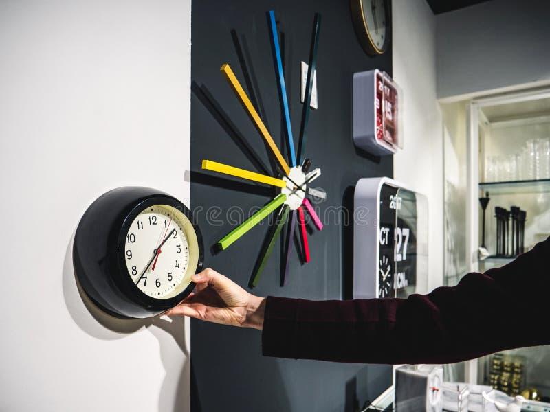 Erntefrau, die Uhr auf Wand wählt stockfotografie