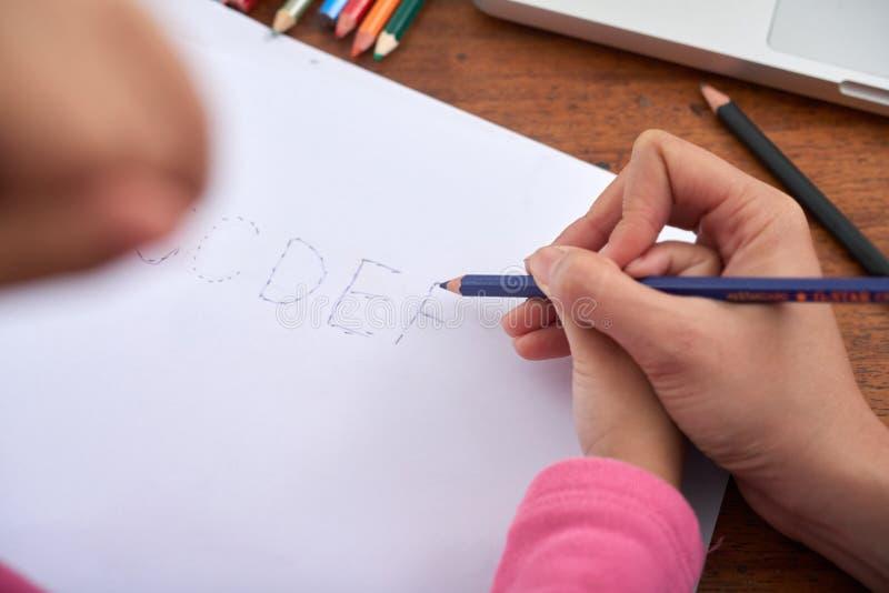 Ernten Sie Hände des Frauen- und Mädchenzeichnungsbuchstaben lizenzfreie stockfotografie