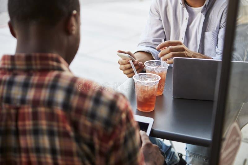 Ernten Sie Schuss von zwei männlichen Freunden mit kalten Getränken außerhalb des Cafés lizenzfreie stockfotos