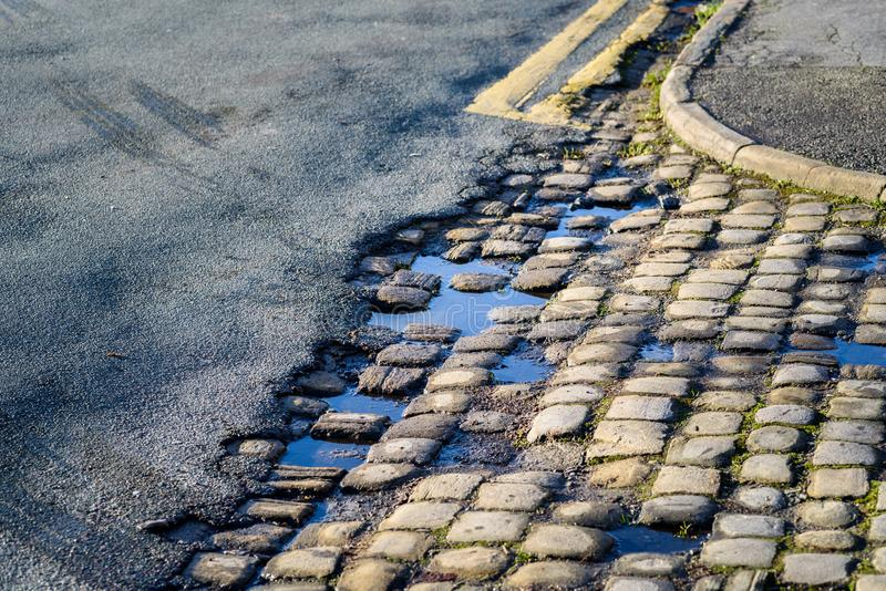 Eroded Road Surface. Eroded tar on road revealing old cobble stones royalty free stock photo