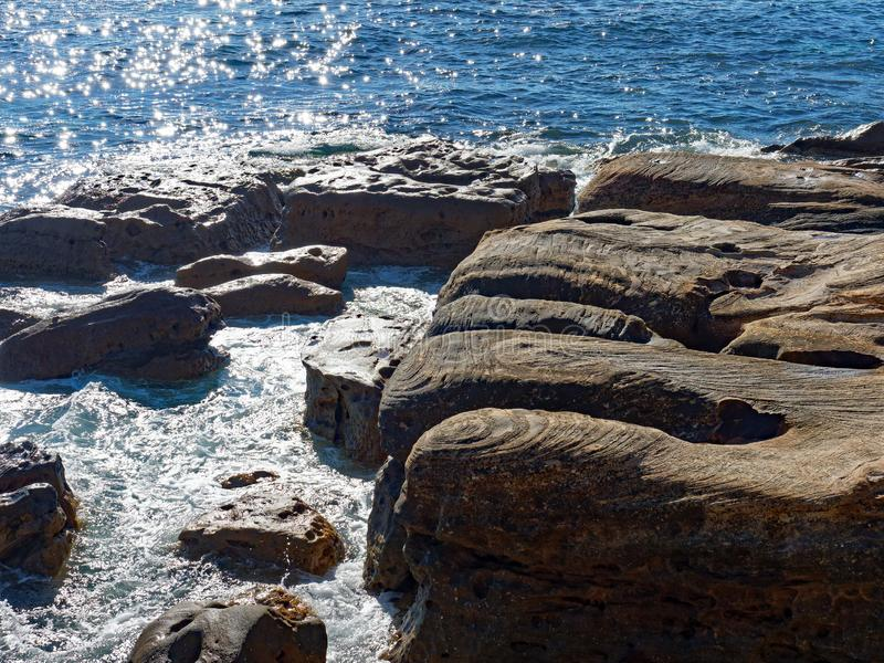 Eroded Sandstone Rocks in Pacific Ocean Waves. Glistening blue Pacific Ocean water washing around weathered and eroded sandstone rocks on the Australian coast royalty free stock image