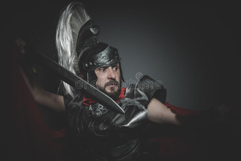 Eroe, legionario romano pretorio e mantello, armatura e spada rossi fotografia stock